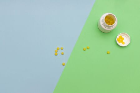 Yellow round jelly beans vitamins on colored background Banco de Imagens