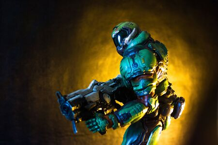SAINT-PETERSBURG,  RUSSIA ─ JULY 15, 2018: Doomguy the protagonist of Doom video game series. Character collection figure on black background. Shallow depth of field, low key photo.
