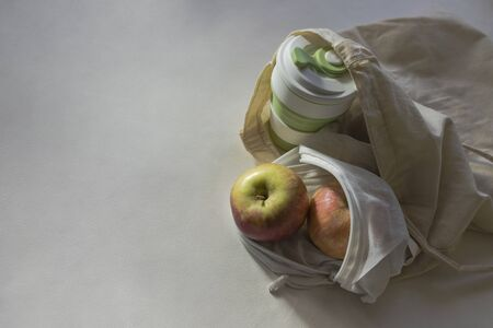 Shopper bag with collapsible silicone mug and apples in reusable fruit pouch on white background in the sunlight with shadows. Concept of trendy environmental-friendly reusable stuff. Place for text