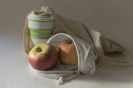 Shopper bag with collapsible silicone mug and apples in reusable mesh bag on white background in the sunlight with shadows. Zero waste concept Stock fotó