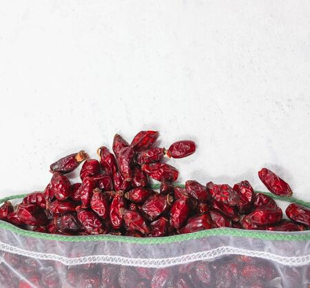 Dried rose hips in mesh bag flat lay on white background. Picture with selective focus and copy space. Healthy eating concept. Plastic free, reusable bag, zero waste concept.
