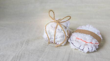 Reusable cotton discs for face or makeup removal tied with twine and packaged in craft paper flat lay. Eco-friendly lifestyle banner, zero waste concept.