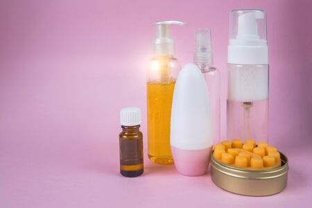 Skin care cosmetics set. Facial wash gel, massage soap, deodorant, essential oil in a bottle cosmetic spray. Front view on pink background with place for text.