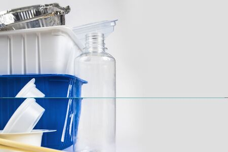 Plastic waste bottles and containers, chopsticks and aluminum container. Recycling garbage on white background Stop plastic concept. Garbage sorting. Single-use plastic objects. Ecological pollution.