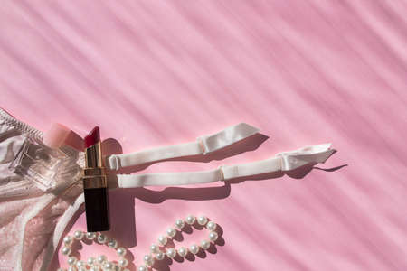 Lingerie garter for stockings, perfume bottle, lipstick and pearl beads. Pink flatlay top view with place for text. Picture with sunbeams. Taking care of yourself. Self-love. Fashionable modern girl stuff