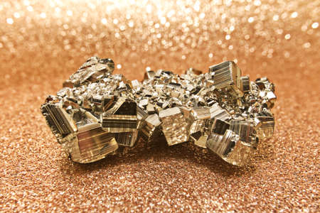 A piece of shiny pyrite on gold background Stock Photo