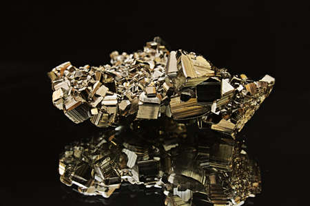 A piece of shiny pyrite with its mirror reflection, on black background