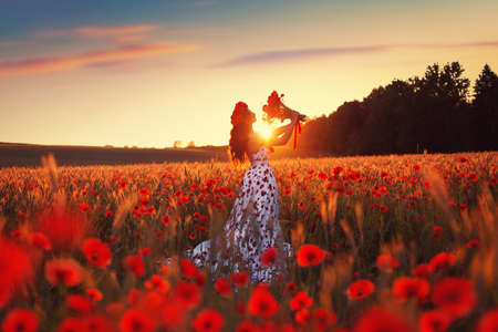 A beautiful young girl in a long dress stands in a poppy field. Silhouette sunset photo. Foto de archivo