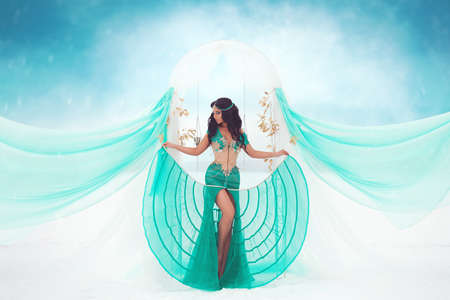 Fantasy portrait of a beautiful tanned brunette girl in a turquoise oriental dress and jewelry, with a bright oriental-style makeup, standing barefoot against the background of an arch, snow and fog