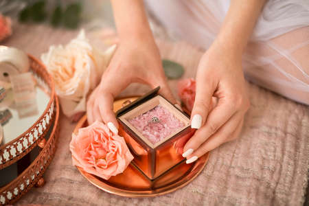 Engagement ring in the bride's hands and the details of the wedding morning: a mirror box with pink sea salt, flowers, jewelry, ribbons, etc.