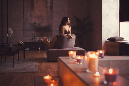 Sexy brunette girl in black lingerie kneeling on a armchair in the interior of a loft style penthouse apartment with a large marble bathroom and lots of candles Banque d'images