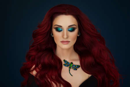 Portrait of a beautiful young red haired girl with with piercings and bright green and blue makeup and a dragonfly brooch around her neck.