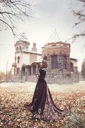 Beautiful young girl in a long vintage dress standing against the background of an old manor. Romantic autumn portrait.