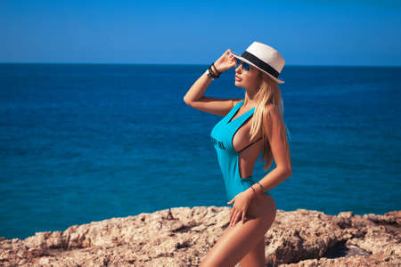 Gorgeous blonde girl in a turquoise swimsuit and white hat on the background of the ocean beach and blue sky