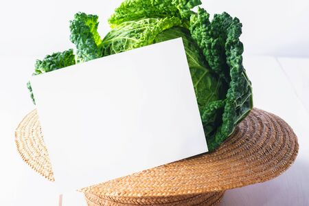 Grenery mock up invitation card or baby card with fresh savoy cabbage in a straw hat on white wooden background, creative food, copy space Stock Photo