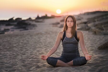 Young blond woman is meditating on a seaside in Healthy Pose on Beach in Sun Light Rays, Yoga Meditation practice concept