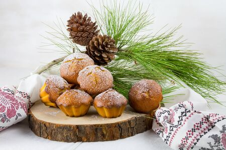 Homemade cristmas cupcake, christmas muffins and new yaer decoration on the wood and light background and pine branches and cones Stock Photo