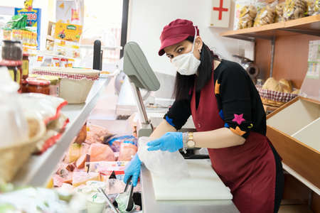Avetrana, Italy, - Marth 16, 2020. Saleswoman is serving a costumer a mozzarella, wearing medical mask and gloves protection during Coronavirus epidemy. Shopping, pandemia of Covid-19, quarantine