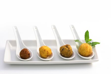 Four ried meat balls in a white plate on white background