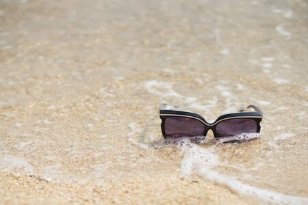 sunglasses in the sea wave on sandy beach, summer holyday relax background, vacation season, copy space