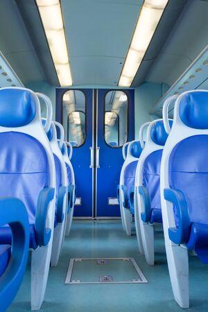 Leerer Innenraum des Zuges für Lang- und Kurzstrecken in Europa, Italien, Zugwagen mit blauen Sitzen, vertikale Ausrichtung