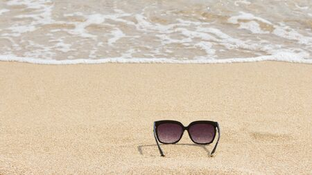 sunglasses on sandy beach, summer holyday relax background, vacation season, copy space