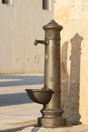 Typical drinking fountain in the south of Italy, Salento, Puglia, drinking water outside in bright sunny afternoon