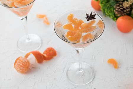 Christmas alcoholic cocktail with tangerines, vodka and star anise, atmospheric New Year's photo with air bubbles