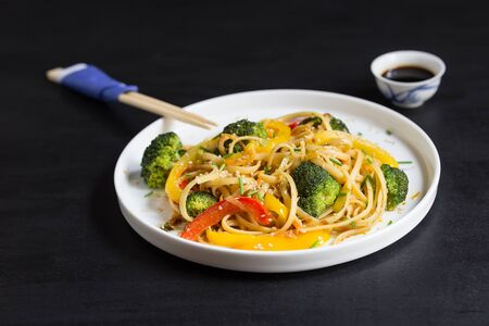 Asia food. Udon noodles with vegetables on the black background, stir fry cooked in wok Фото со стока