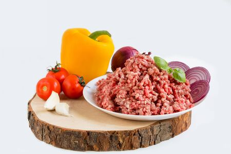 fresh raw minced beef in a plate close up on a rustic wooden cutting board, with peppers, onion and tomatoes