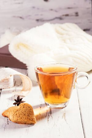 A cup of hot tea with some anise and cinnamon over a wood table. Concept of winter compfort, autumn mood