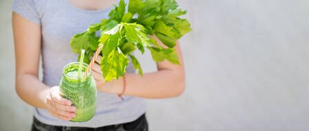 A young girl holds a jar of green smoothie and fresh celery in her hands. Summer vitamin and nutritious drink for the whole family. Detox and healthy eating concept Banque d'images