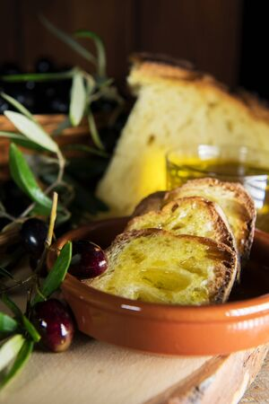 Slices of bread in a plate of terracotta covered by Extra Virgin Olive Oil from Puglia, Salento, Italy. Tradicional starters of mediterranean diet. healthy organic food, vertical image Reklamní fotografie