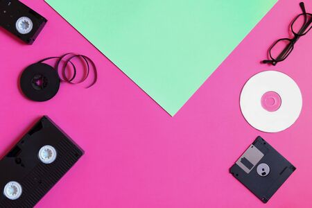 Retro storage devices: plate, two videocassette, floppy disk, CD and glasses. Outdated technology concept on pink and mint paper background, top view, minimalism, copy space 版權商用圖片