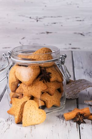 Edible gift. Ginger cookies shaped as hearts and stars in a jar with some anise and cinnamon. The jar is over a wood table. Concept of Christmas family baking, zero waste and winter compfort