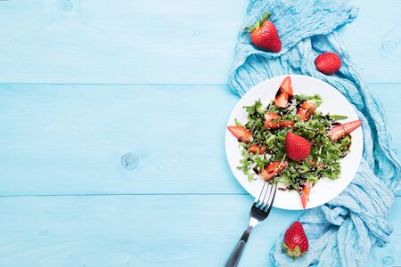 Healthy organic diet salad with arugula, strawberries and sesame with balsamic glaze in white plate on a pastel blue wooden background, top view, scandinave style, healthy food clean eating concept