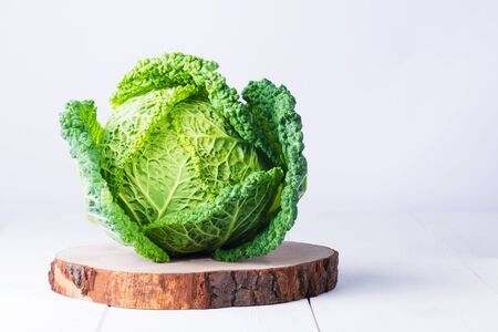 Fresh savoy cabbage in a hat on white wooden background, creative food, copy space