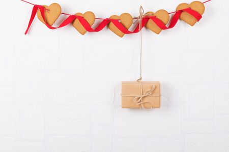 Heart shaped cookies and a gift hanging on a white wall. Simbol of cozy love and Valentines Day backrgound and festive and birthday concept, greeting card, copy space