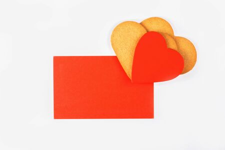 Red mockup greenting card with heart shape cookies on a white backround. Simbol of cozy love and Valentines Day backrgound and festive and birthday concept, copy space