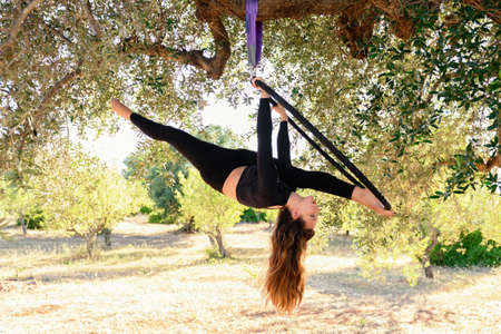 Acrobat, young girl making a split on an aerial hoop among olive trees in summer. Acrobat training during summer, outdoors.