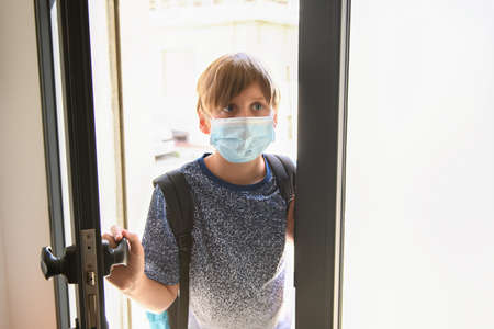 A boy wearing a medical mask open the door for enter in school, back to school during pandemic of Covid-19, new normal Foto de archivo