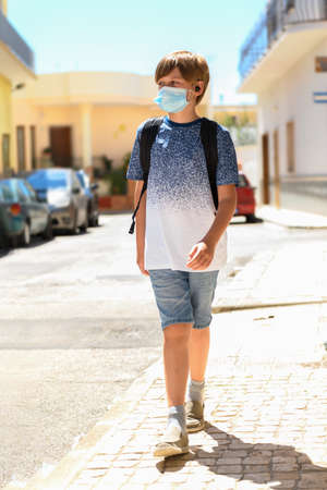 A boy wearing a medical mask go to school in the empty sunny street, back to school during pandemic of Covid-19
