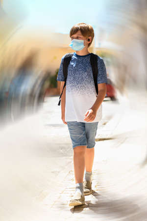 A boy wearing a medical mask go to school on a blured rotation background, back to school during pandemic of Covid-19, transition to new normal and new coronavirus reality