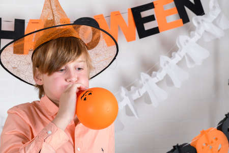 A blond boy in orange hat inflates one orange balloon, decorates his room to celebrate Halloween at home on a white brick wall background.