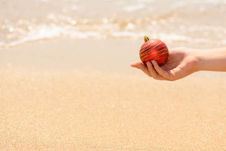 female hand holding a red Christmas ball on the ocean wave background