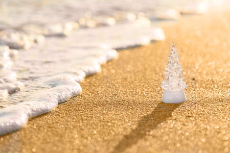 Christmas tree glass decoration on the golden beach. Christmas tropical concept., summer Christmas and winter holyday concept