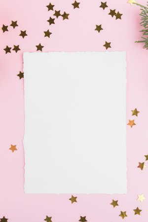 Christmas card mockup template with fir twigs and golden stars and festive decoration on a pink pastel background. Design element for CHristmas and New Year congratulation