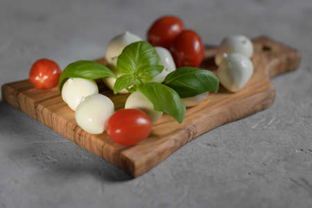 close up of fresh apulian mozzarella cheese on a wooden cutting board with fresh leaf of basil, close up and selective focus, food made in Puglia, Italy