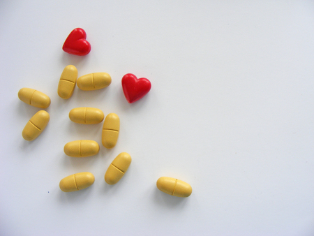 pills and red hearts on white background with place for writing