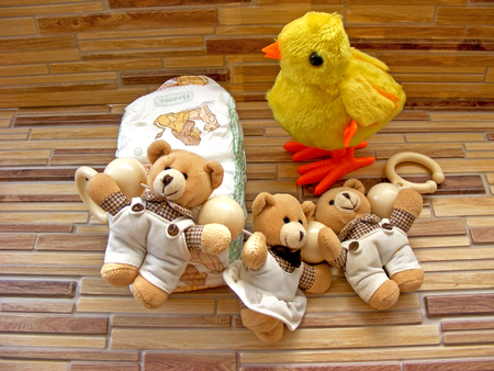 Child stack of diapers, chiken and teddy bear toy on a bamboo background Stock Photo